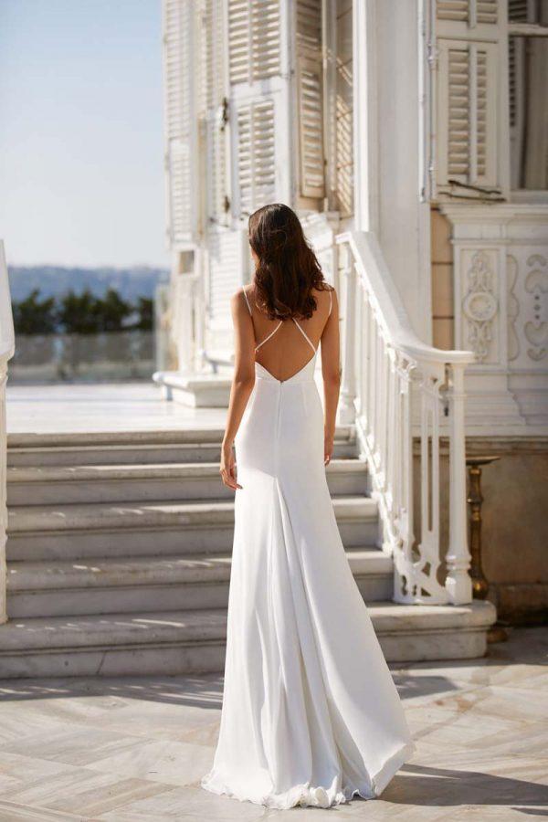 Vjenčanica laganog i lepršavog materijala, blagog A kroja. s s tankim bretelama koje se križaju na otvorenim leđima.