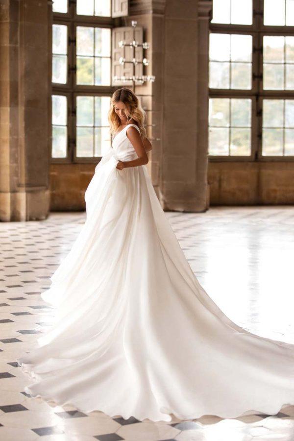 Vjenčanica bez rukava koja naglašava struk i lijepu figuru, ima duboki dekolte i dugački elegantni šlep.