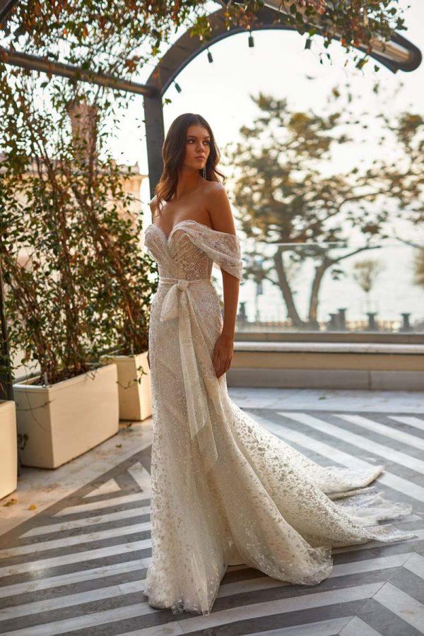 Vjenčanica od svjetlucave čipkane haljine u ivory boja s vezenom elegantnom mašnom oko struka.
