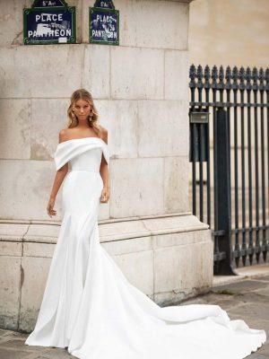 Vjenčanica s otvorenim ramenima i blago padajućim rukavima od materijala koji se na leđima veže u veliku elegantnu mašnu.
