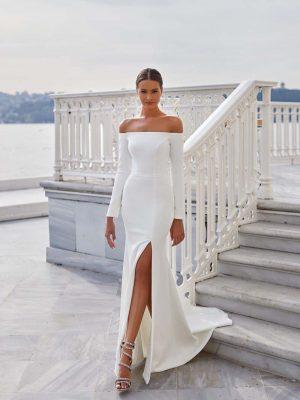Vjenčanica sirena kroja, s dugačkim rukavima, dubokim prorezom od bedara duž nogu i elegantno otvorenim ramenima.