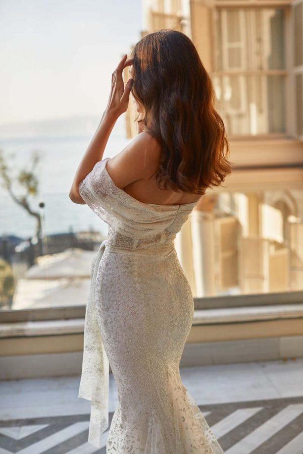 Vjenčanica od svjetlucave čipkane haljine u ivory boja s vezenom elegantnom mašnom oko struka. i padajućim rukavima.