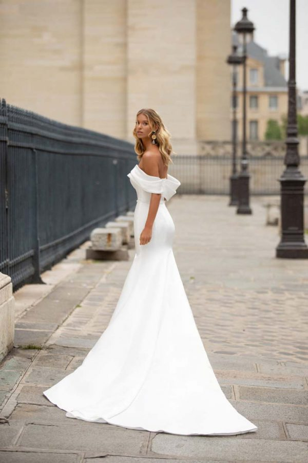 Vjenčanica s otvorenim ramenima, dugim šlepom i blago padajućim rukavima od materijala koji se na leđima veže u veliku elegantnu mašnu.